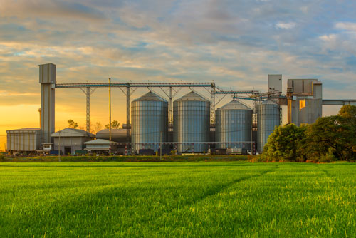 Farm with silos with sunset in background