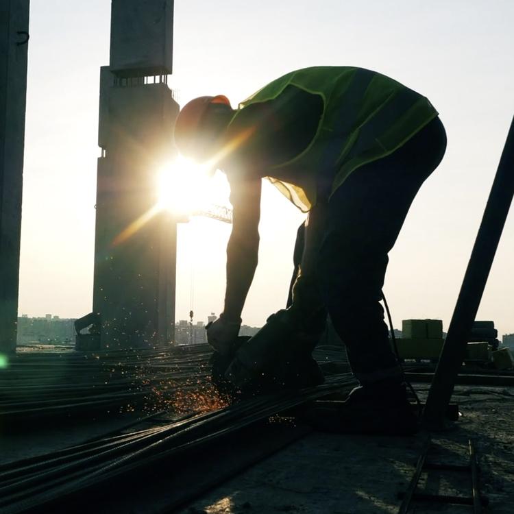 Man welding with sunshine behind