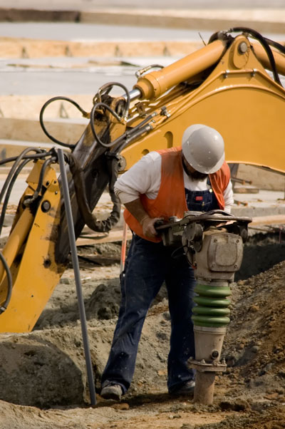construction worker drilling into ground